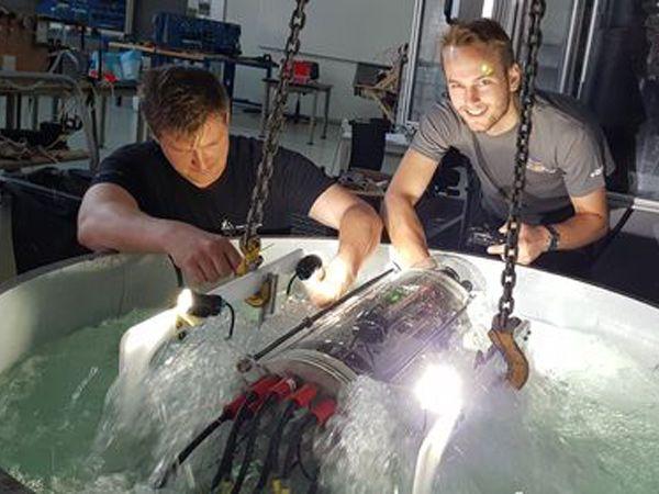 De tre studerende fra Aarhus Universitet og deres undervandsrobot vækker international anerkendelse.Her tjekker Johan T. Krogshave (t.v.) og Robert Søndergaard (t.h.) de grundlæggende funktioner på robotten i et testbassin. (Foto: Jesper Bruun)