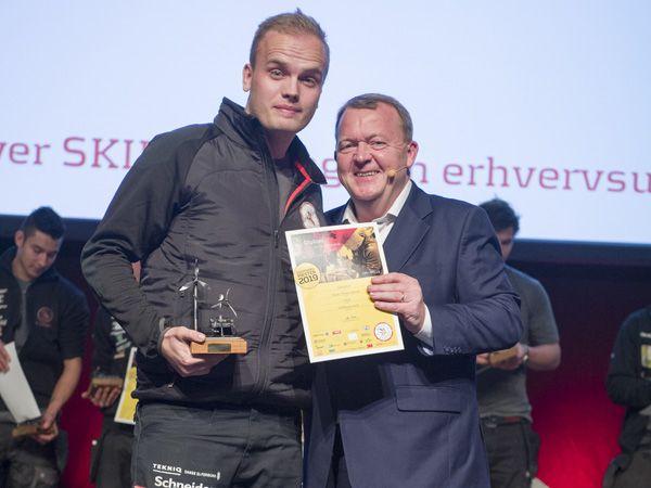 Årets vinder af Danmarksmesterskabet for elektrikerlærlinge, Jonas Thrane Bendt, får her overrakt det synlige bevis af statsminister Lars Løkke Rasmussen. (Foto: SkillsDenmark/Per Daugaard)