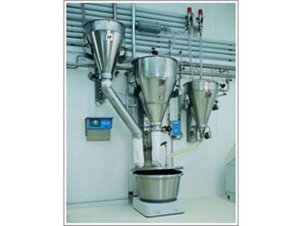 Eksempel på en kombineret vejestation inklusive en 100 kilogram modtagebeholder med udløbsrør til småingredienser (Billedet t.v.), en 250 kilogram vejebeholder med pneumatisk tømmehjælp og spjæld, automatisk filterrenseenhed og støvlåg (i midten), samt en 140 liter væskevægt (t.h.). Vision 2000 receptcomputeren, som er koblet op med B48-vandblanderen, ses på væggen.