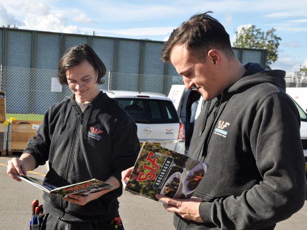 SIF Gruppen har produceret sin helt egen kogebog, hvor medarbejderne har bidraget med deres bedste sommeropskrifter og billeder. Lærling Klaus Skandov (t.v..) og elektriker Amir Dubica bladrer her i de nye kogebøger.