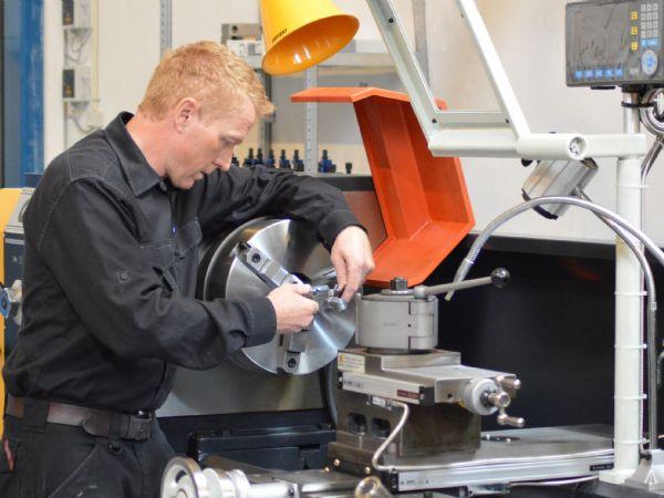 Hydra-Comps reparationsafdeling i Kolding er udstyret med en til faget hører egnet maskinpark, som eksempelvis drejebænken, som Aksel Madsen her ses i aktion ved.