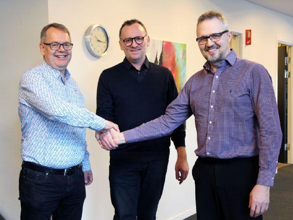 Direktør Mads A. Velbæk (t.v.) og direktør Michael Johansen giver håndslag på aftalen med Henrik Østerlin (t.h.), der fremadrettet bliver Key Account Manager i Østdanmark hos MTO electric.