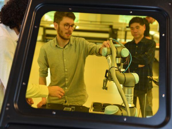 AU-ingeniørstuderende og ph.d.-studerende arbejder her på robotarmen under vejledning fra lektor Xuping Zhang (t,h,). (Foto: Jesper Bruun)